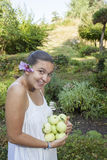 Cute girl holding green apples. Cute natural looking young woman holding organic apples  in her beautiful feng shui garden with bonsai pine tree in the Royalty Free Stock Images