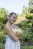 Cute girl holding green apples and pears. Cute natural looking young woman holding organic apples and pears in her beautiful feng shui garden with bonsai pine Stock Photo