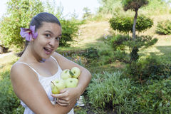 Cute girl holding green apples and pears. Cute natural looking young woman holding organic apples and pears in her beautiful feng shui garden with bonsai pine Royalty Free Stock Photo