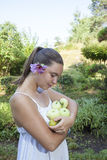 Cute girl holding green apples and pears. Cute natural looking young woman holding organic apples and pears in her beautiful feng shui garden with bonsai pine Royalty Free Stock Images