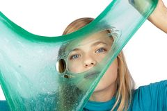 Cute girl holding a green slime with a hole in front of her face. Cute girl holding a green slime in front of her face and looking through it. Studio shot royalty free stock image
