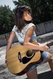 Cute girl holding guitar royalty free stock photos