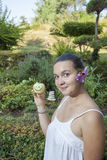 Cute girl holding happy apple. Cute natural looking young woman holding smiling organic apple in her beautiful feng shui garden with bonsai pine tree in the Stock Photography
