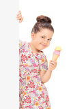 Cute girl holding an ice cream behind a panel Stock Photo