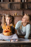 Cute girl holding jack o lantern being near her mother. Look what we have. Pleasant delighted little girl holding the pumpkin while sitting on the table in the Royalty Free Stock Photography