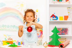 Cute girl holding New Year ball and brush. Cute girl holds New Year ball and brush while standing alone at the white table with decorations on it and carton Stock Photography