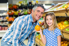 Cute girl holding an orange to her father Stock Images