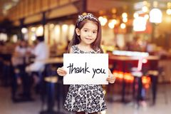 Cute girl holding a piece of paper with the words Thank You. Blur restaurant background stock images