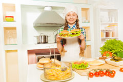 Cute girl holding plate with hamburgers at kitchen Stock Photography