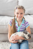 Cute girl holding rabbit in living area Stock Photos