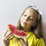 A cute girl holding a ripe watermelon. Royalty Free Stock Image