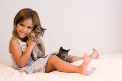 Cute girl holding tabby kitten on soft off-white comforter. Cute little four year old girl holding a tabby kitten with another kitten in front of her, sitting on Royalty Free Stock Image