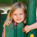 Cute girl holding on to wooden fence. Stock Images