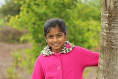 Cute girl holding tree trunk Royalty Free Stock Photography