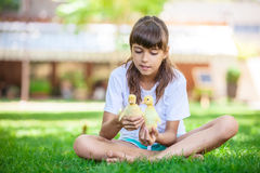 Cute girl holding two spring ducklings Stock Photo
