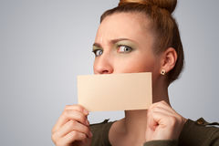 Cute girl holding white card at front of her lips with copy spac Stock Photography