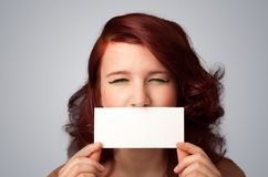 Cute girl holding white card at front of her lips with copy spac Royalty Free Stock Photography