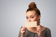 Cute girl holding white card at front of her lips with copy spac Stock Images