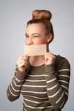 Cute girl holding white card at front of her lips with copy spac Stock Photos