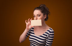 Cute girl holding white card at front of her lips with copy spac Royalty Free Stock Photos