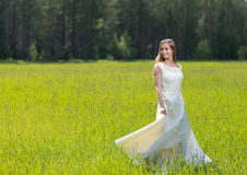 Cute girl holding white dress in green field Stock Photos
