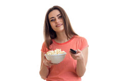 Cute girl holds bowl of pop corn and switch remote control channels. Is isolated on a white background stock image