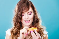 Cute girl holds fruit cake in hand on blue Royalty Free Stock Photo