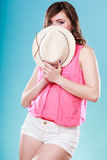 Cute girl holds summer straw hat covering her face Stock Photo