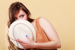 Cute girl holds summer straw hat covering her face Stock Image