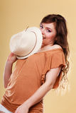 Cute girl holds summer straw hat covering her face Royalty Free Stock Photos