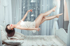 Cute girl hovers over the bed. Royalty Free Stock Images