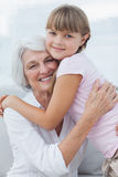 Cute girl hugging her grandmother Stock Images