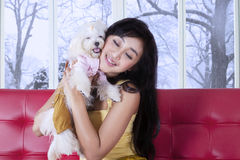 Cute girl hugging her puppy on the sofa Royalty Free Stock Photo