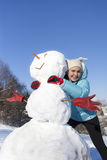 Cute girl hugging  the snowman Royalty Free Stock Photography