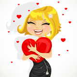 Cute girl hugging a soft pillow-heart Royalty Free Stock Photography