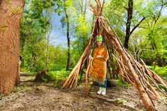 Cute girl in Indian costume standing at the tepee. Portrait of cute girl in Indian costume standing at the tepee in the forest Stock Image