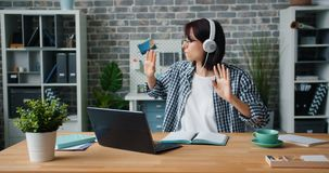 Cute girl listening to music in headphones dancing working with laptop in office. Cute girl joyful employee is listening to music in headphones dancing working stock video footage