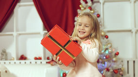 Cute girl jumping from happiness getting a gift for the new year Stock Photography