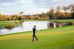 Cute girl jumping and running on the green grass of the golf cou. Rse. Outdoor shot, autumn. Good sunny day Stock Photo