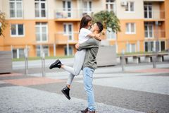 Cute girl jumping to man sunny, summer day. Stylish couple in love hugging and kissing in city street. Relationship, active lifest Royalty Free Stock Images