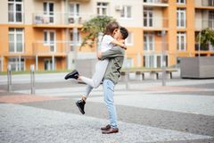 Cute girl jumping to man sunny, summer day. Stylish couple in love hugging and kissing in city street. Relationship, active lifest Stock Image