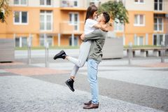 Cute girl jumping to man sunny, summer day. Stylish couple in love hugging and kissing in city street. Relationship, active lifest Stock Photo