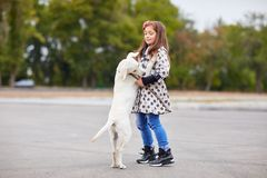 Beautiful little lady playing with dog outdoors. Pet concept. Cute girl kid with doggie playing on the street. Having fun together outdoors on the nature Stock Images