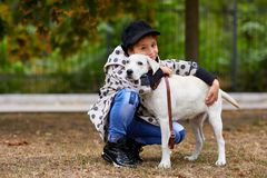 Beautiful young girl playing with dog outdoors. Pet concept. Cute girl kid with doggie walking in the park. Having fun together outdoors on the nature Royalty Free Stock Photo
