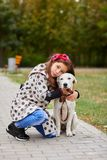 Beautiful young girl playing with dog outdoors. Pet concept. Cute girl kid with doggie walking in the park. Having fun together outdoors on the nature Stock Image