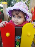Cute toddler with pink hat on playground. Cute girl on kindergarten climbing on playground and slide peeking out Stock Images