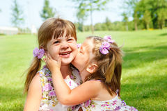 Girl kissing her sister royalty free stock photos
