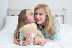 Cute girl kissing her smiling mother Stock Photos