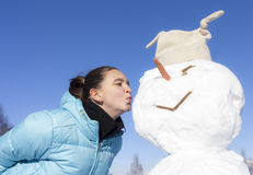 Cute girl kissing the snowman Royalty Free Stock Images