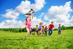 Cute girl with kite run with friends Stock Photos